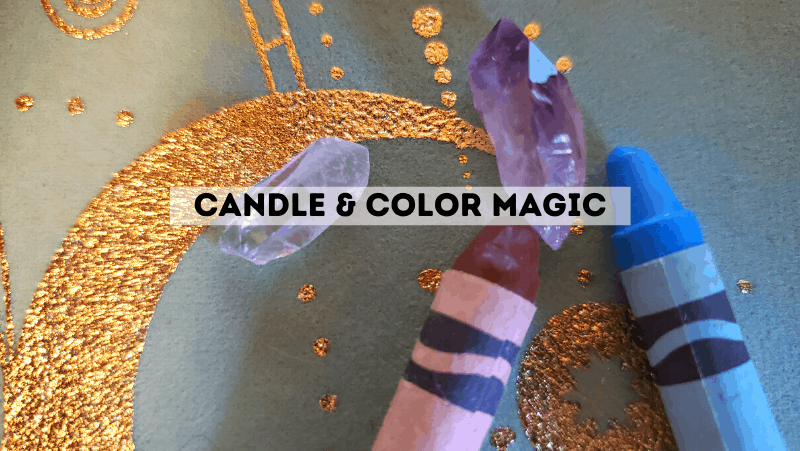 A brown crayon, blue crayon, and two crystals on an occult witch cloth