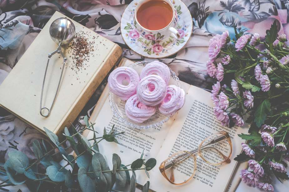 floral ceramic cup and saucer above open book