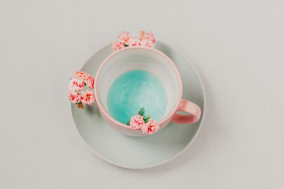 pink cup with blue liquid and pink flowers