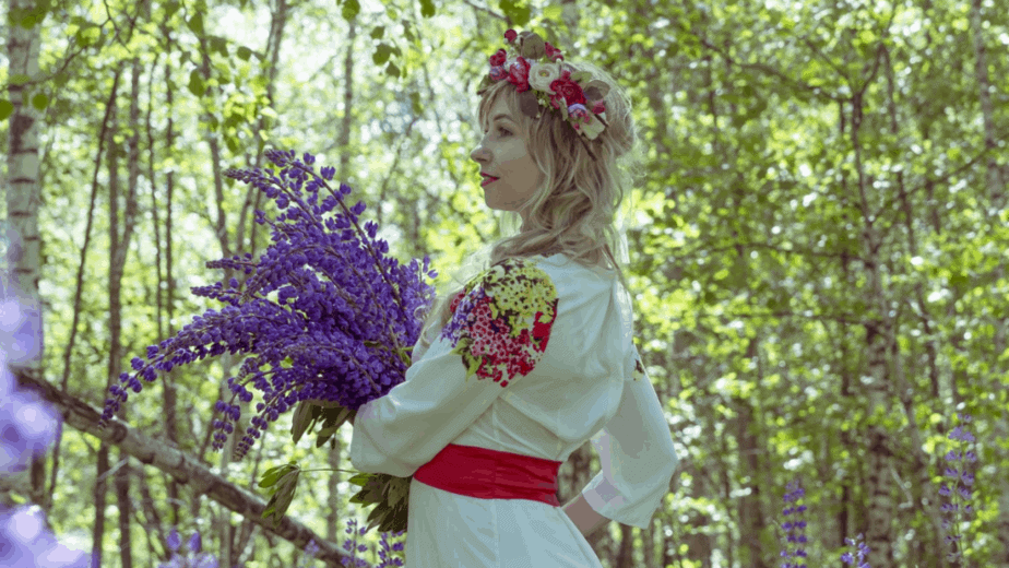 Decorative image of a woman in cultural dress holding flowers and wearing a flower crown