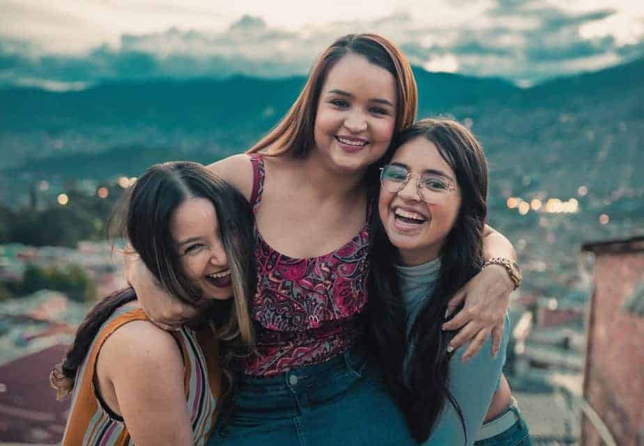happy young women hugging on rooftop