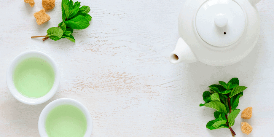 Decorative image of green tea in cups, mint leaves, candied ginger, and a ceramic tea kettle. Herbal iced tea.