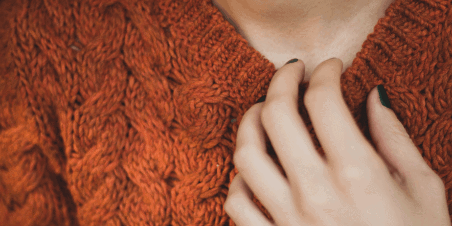 Decorative image of a woman in a brown sweater with her hand to her chest