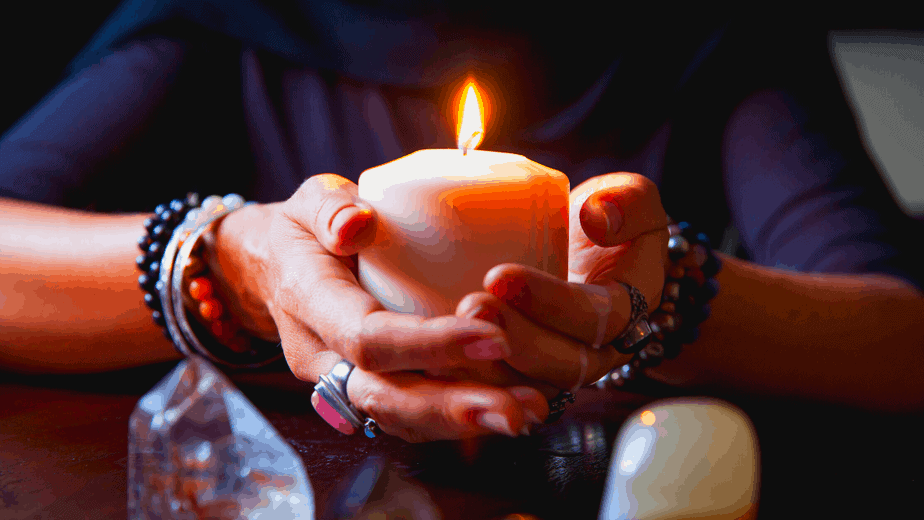 Decorative image of a woman holding a candle surrounded by crystals