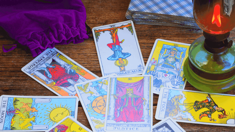 Decorative image of tarot cards spread on a table with a gas lamp