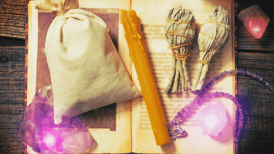 Decorative image of a spell bag, a book of shadows, smoke cleansing supplies, crystals, and a candle