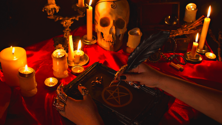 Decorative image of a pagan altar with a book of shadows, feather dip pen, skull with pentacle, red velvet altar cloth, and more