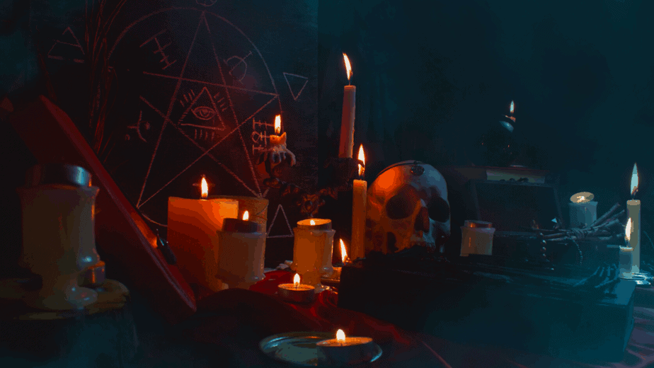 Decorative image of a witch's altar with lit candles, a pentacle, and religious symbolism