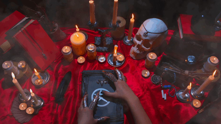 Decorative image of a witch's altar with a skull, pentacle, candles, red velvet altar cloth, and more