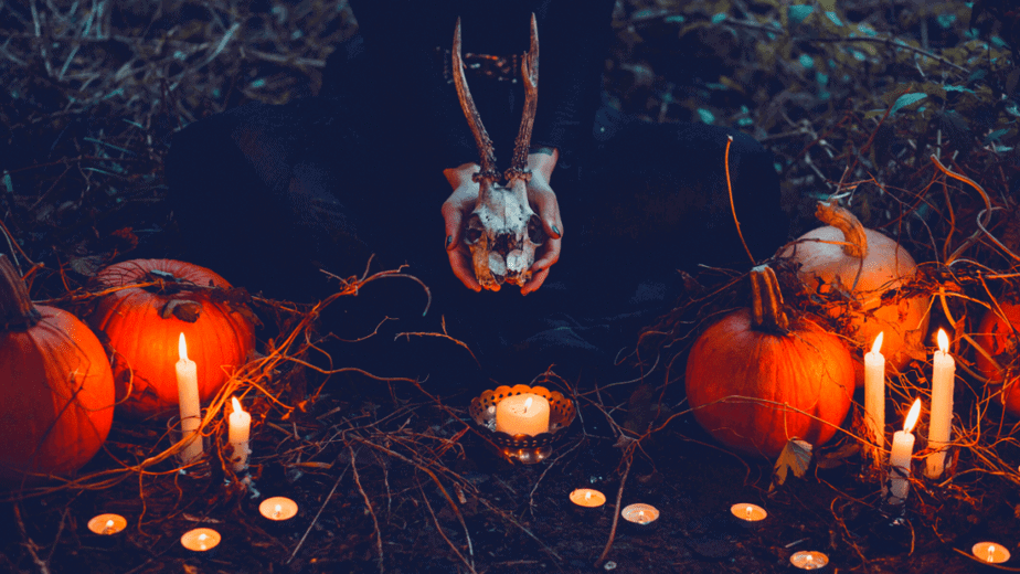 Decorative image of a witch holding a skull and surrounded by lit candles and pumpkins