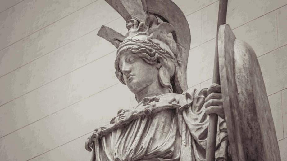 Decorative image of a statue of the Greek goddess Athena in armor and holding a shield and spear