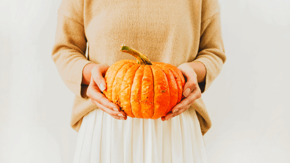 Decorative image of a woman holding a pumpkin for Mabon