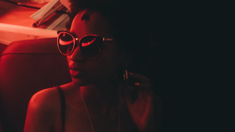 Decorative image of a black woman in sunglasses and red light cast on her