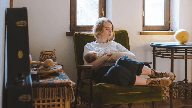 Decorative image of a woman breastfeeding an infant in a hygge cozy bedroom