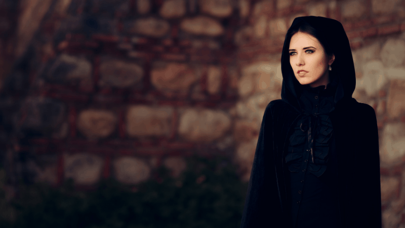A female witch in a black cloak looking off into the distance