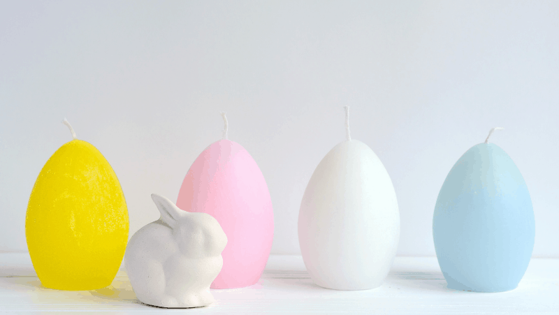 Egg candles in pastel colors with a white ceramic bunny rabbit.