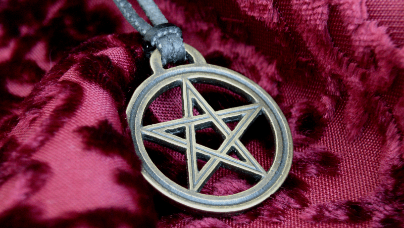 A pentacle necklace on leather rope and sitting on purple or red fabric
