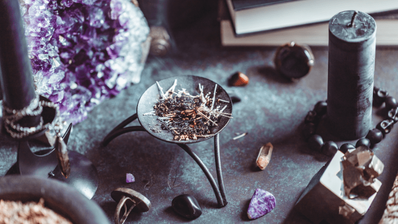 Witch supplies on an altar, including incense, crystals, jewelry, and candles