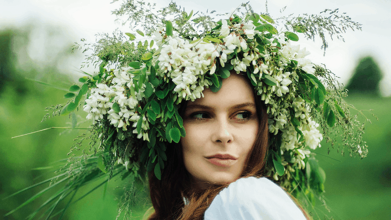 A pagan woman looking to the side and wearing a flower crown.