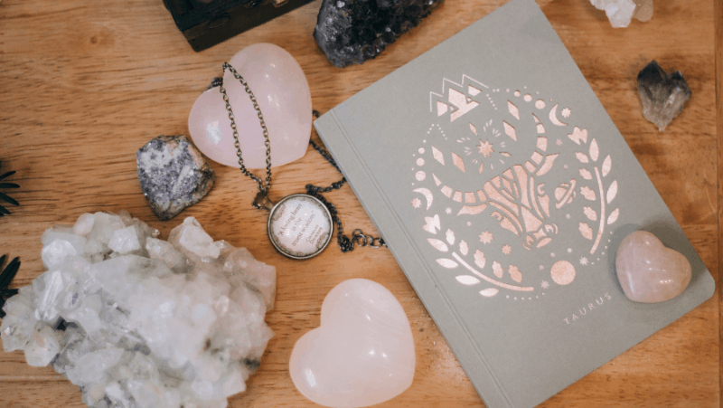 Rose quartz and other crystals on a flat lay with a taurus journal