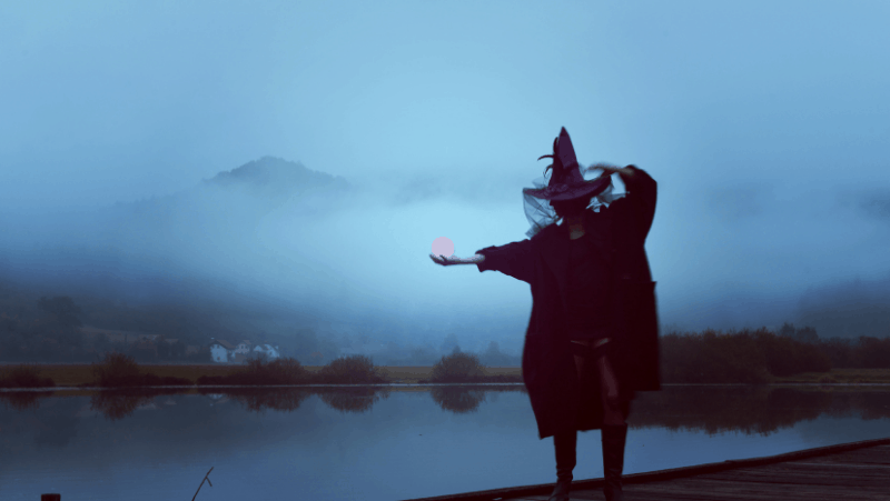 Yule gifts for witchy friends include crystal balls and big witch hats, like the one this woman is wearing while she is out on a dock by a foggy lake.
