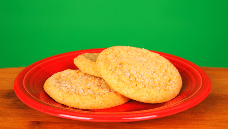Sugar cookies on a red plate with a green background.