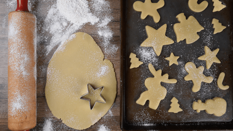 A rolling pin dusted with flour. Sugar cookie dough rolled out with a star cookie cutter on it. Sugar cookies shaped like reindeer, gingerbread men, angels, stars, trees, and snowmen.
