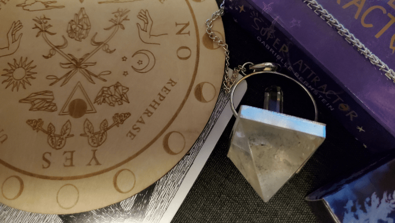 A magical pendulum, a tarot card, and a wooden pendulum board from Tamed WIld