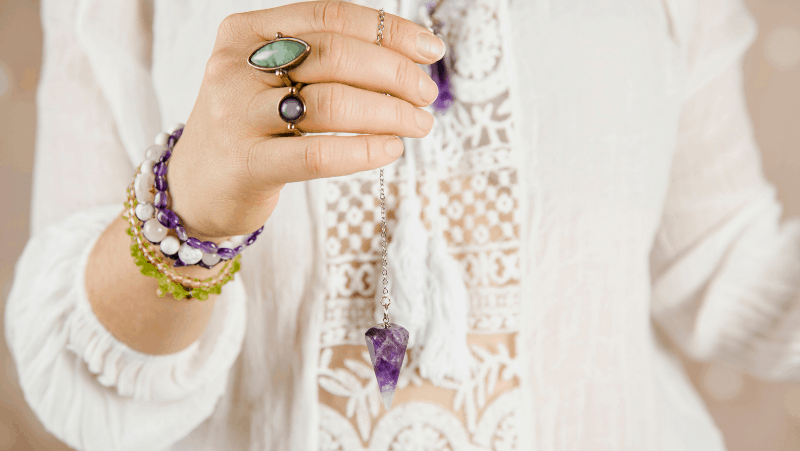 A woman with an amethyst pendulum wearing a preppy sweater and many crystal bracelets and rings