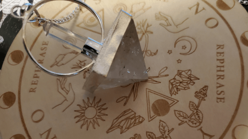 A quartz pendulum pyramid resting on a wooden pendulum board that came in a Tamed Wild box