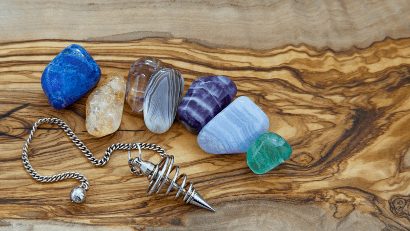 A silver pendulum and 7 colorful spiritual crystals for healing