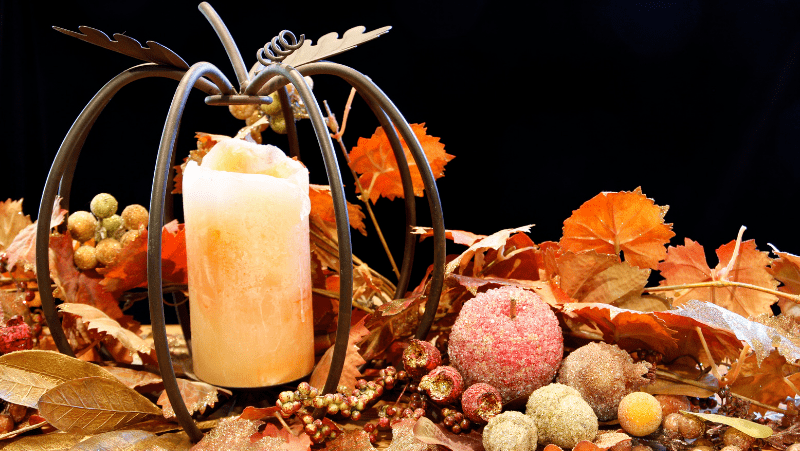 A wire metal pumpkin with a candle inside surrounded by candied fruits and fake fall leaves