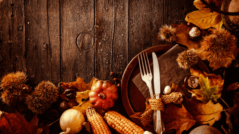 A Thanksgiving spread with a brown plate and a fork and knife wrapped with jute ribbon surrounded by corn, leaves, conkers, and acorns on a wooden table