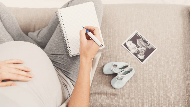 A pregnant woman with an ultrasound, baby shoes, and a notebook