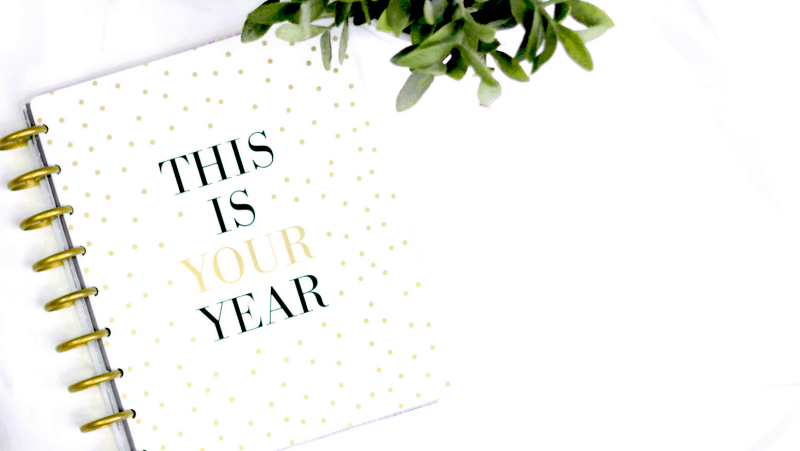 """A planner on a white background with a plant. The planner says """"this is your year"""""""