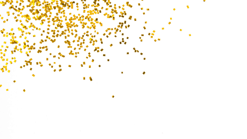 Gold confetti on a white background. Pagan new year traditions include drinking, writing in journals, and new year rituals.