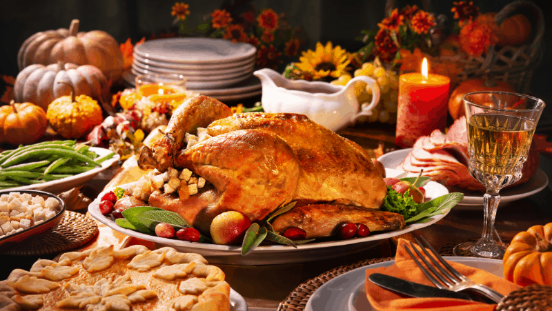 What do witches do for Thanksgiving? They eat turkey like this one in this image, surrounded by other Thanksgiving foods and drinks and a lit candle