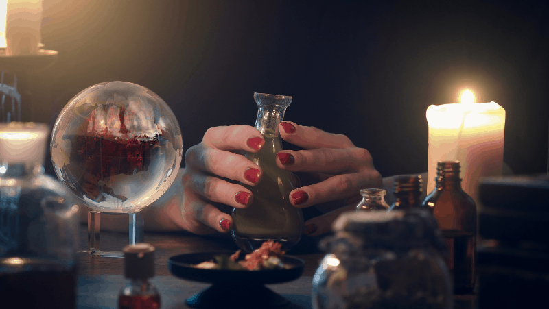Witchy hands holding a spell jar next to a crystal ball and candle