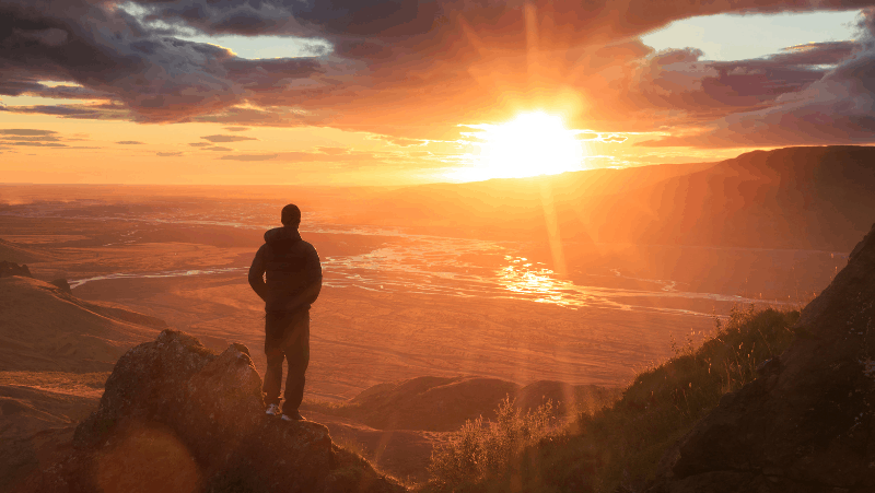 A hiker looking out over the mountains at the sun