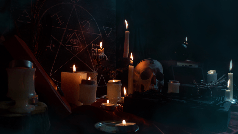 A table set with witchy tools like a skull, pentagram, candles, and more