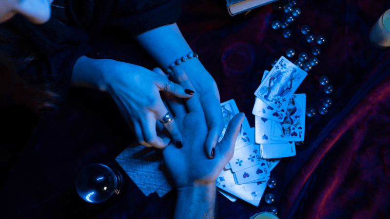 Someone reading palms on a table covered with crystals and cards