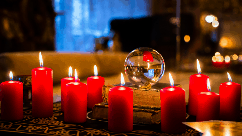 A table with lit red candles, books, and a crystal ball