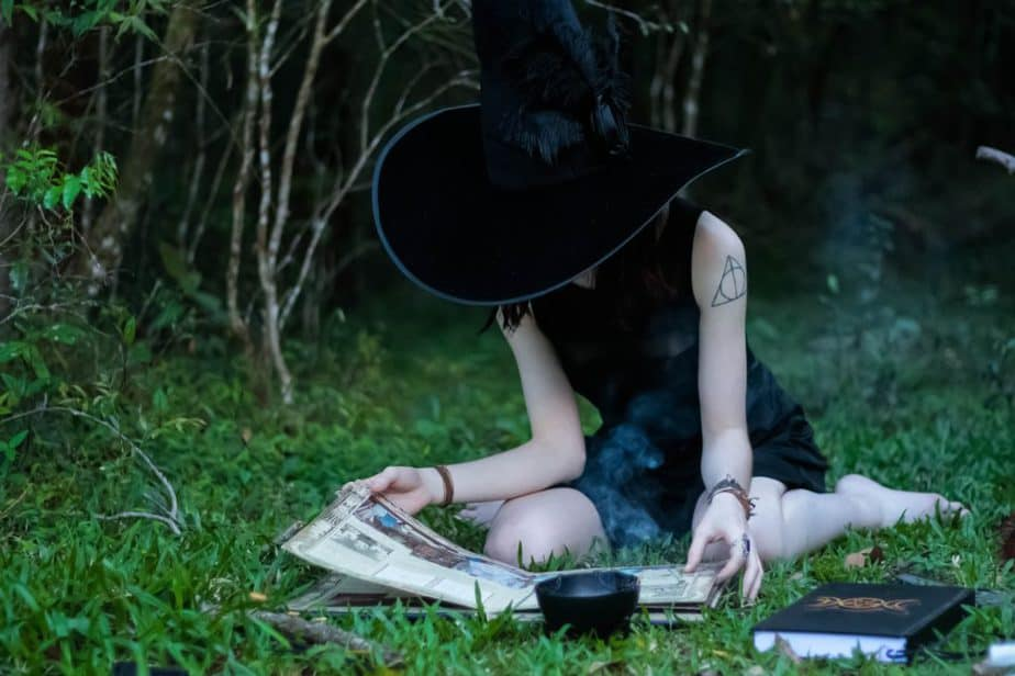 woman reading book on the anatomy of a spell while sitting on green lawn grasses