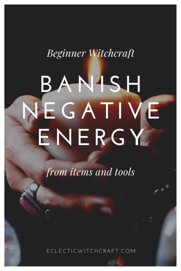 Beginner witchcraft: banish negative energy from items and tools. A witch holding a white candle and wearing jewelry.