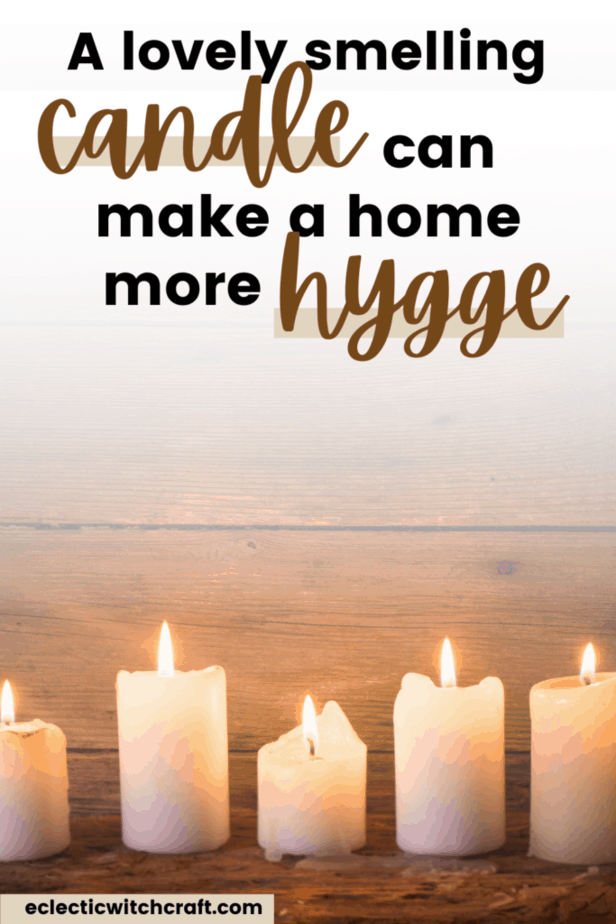 A lovely smelling candle can make a home more hygge. A line of white candles lit with fire against a wooden background.
