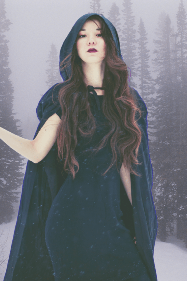 A witch in a hooded cloak performing January magick with herbs. She is in a foggy forest.