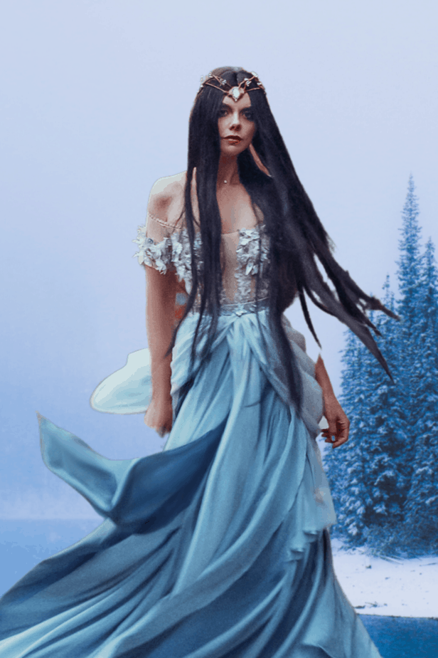 A sorceress in a whispy white dress with long black hair and a diadem in a snowy landscape