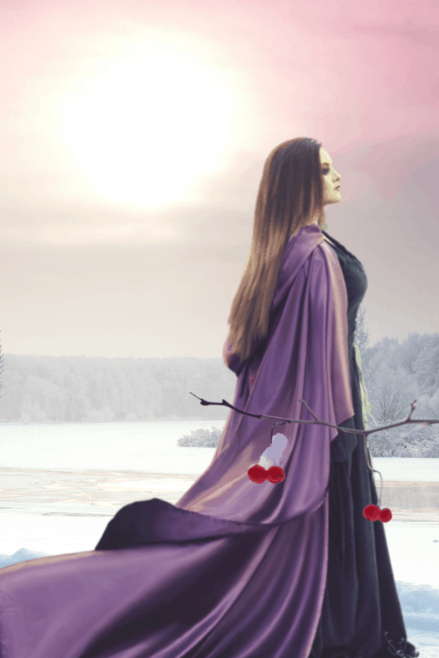 A witch in a purple cloak behind winter berries in a hazy winter landscape sunrise