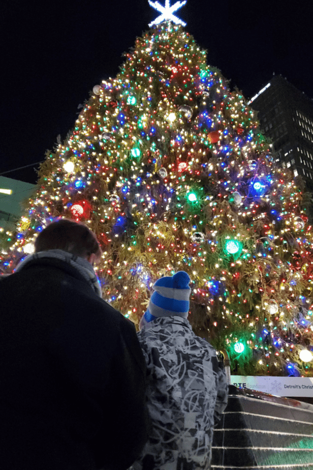 A large Christmas tree lit up in downtown Detroit with a child and adult man standing in front of it.
