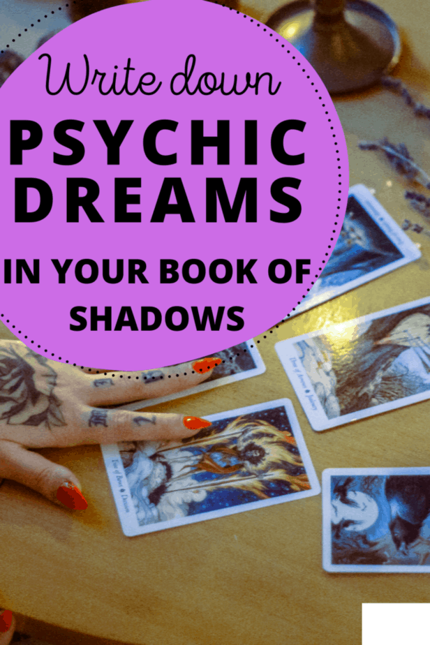 Write down psychic dreams in your book of shadows. A tarot reader with tattoos on her hands and red nails reading tarot cards.